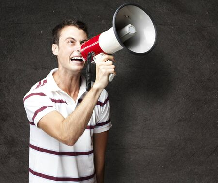 portrait of young man shouting with megaphone against a grunge wall Stock Photo - 12656295