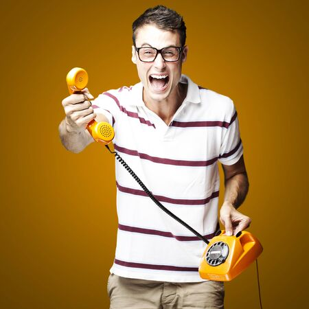 portrait of young man offering vintage telephone to call over orange background photo