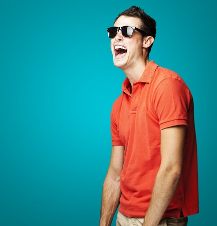 human teeth: portrait of young man with sunglasses laughing over blue background
