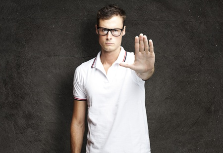 five fingers: portrait of a handsome young man doing stop symbol against a grunge wall Stock Photo