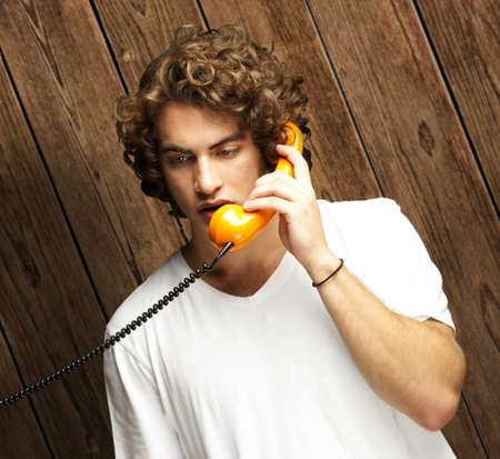 portrait of young man talking on a vintage telephone against a wooden wall photo