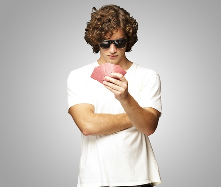 cards deck: young man holding cards and wearing sunglasses against a grey background