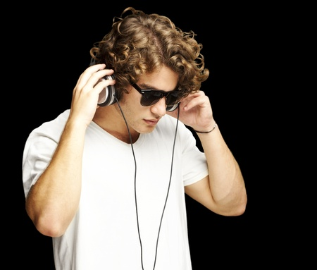 portrait of a handsome young man listening music against a black background photo