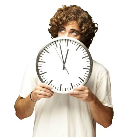 scared young man hidden behind a clock against a white background photo