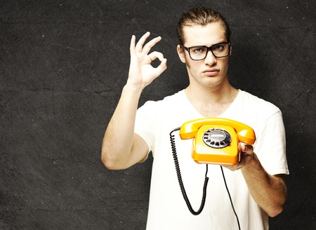 young man holding a vintage telephone and gesturing against grunge background photo