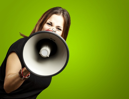 public speaking: portrait of young woman shouting with megaphone over green
