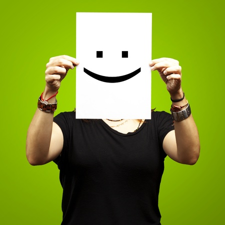 Woman showing a blank paper with a smile emoticon in front of her face against a green background photo