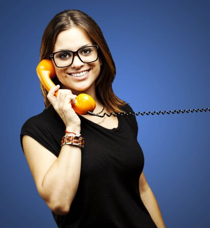 portrait of young woman talking using vintage telephone over blue background Stock Photo - 12656132