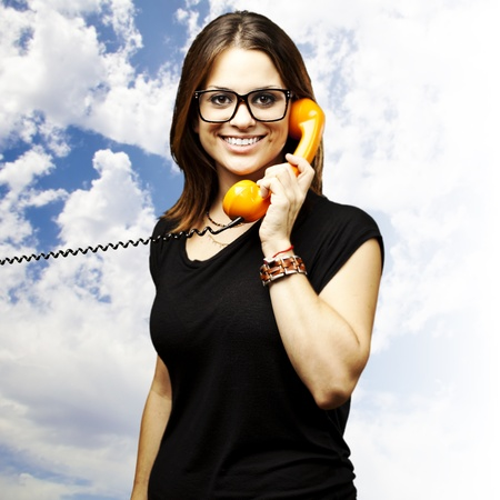 portrait of young woman talking using a vintage telephone against a blue sky background photo
