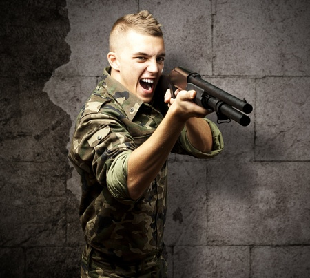 portrait of a young soldier aiming with shotgun against a grunge background photo