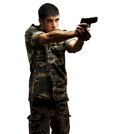 portrait of a young soldier aiming with pistol against a white background photo