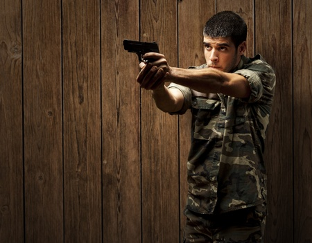 portrait of a young soldier aiming with pistol against a wooden wall photo