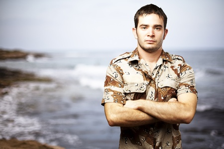portrait of a serious young soldier standing against a sea background photo