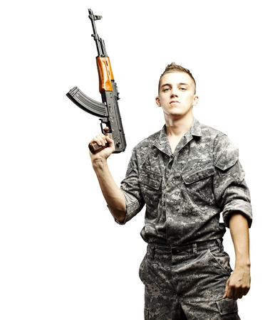 man holding gun: portrait of young soldier holding rifle wearing urban camouflage over white background