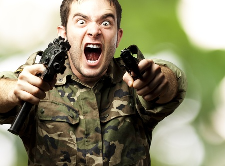 man holding gun: portrait of a young soldier aiming with pistol against a abstract background