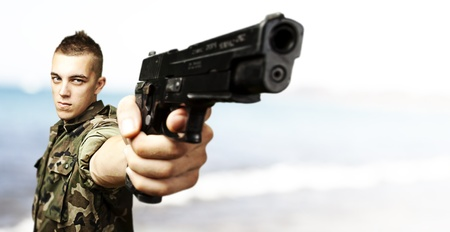 portrait of young soldier aiming with gun landing on a island photo