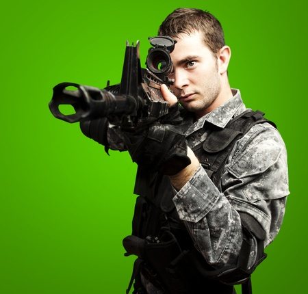 portrait of young soldier aiming with rifle over green background Stock Photo - 12656203