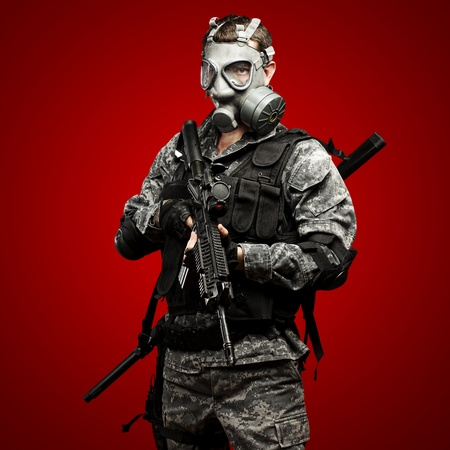 portrait of young soldier with gas mask and rifle against a red background Stock Photo - 12603863