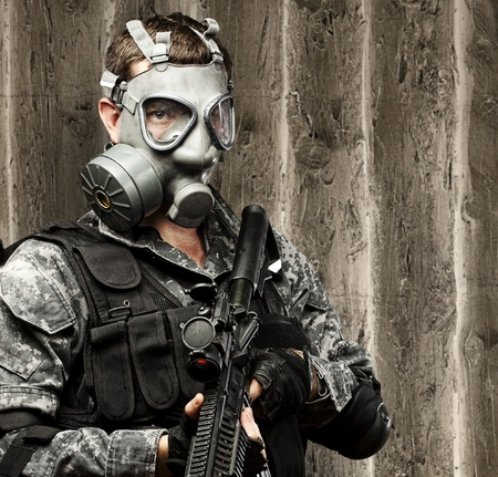 portrait of young soldier with gas mask and rifle against a grunge wooden background photo