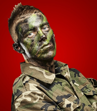 face paint: portrait of young soldier with jungle camouflage paint on a red background