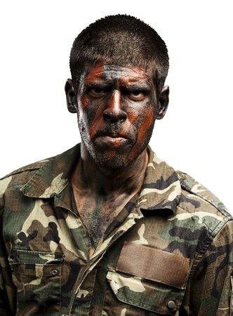 young soldier with camouflage paint looking very serious over white photo