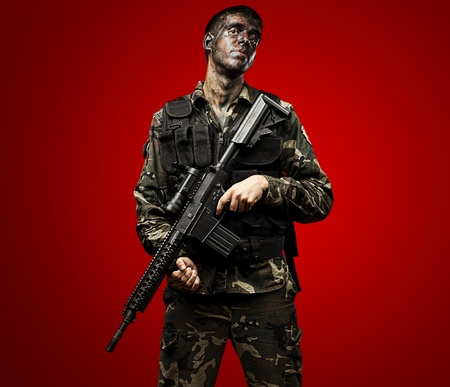 portrait of young soldier painted with jungle camouflage holding riffle over red background photo