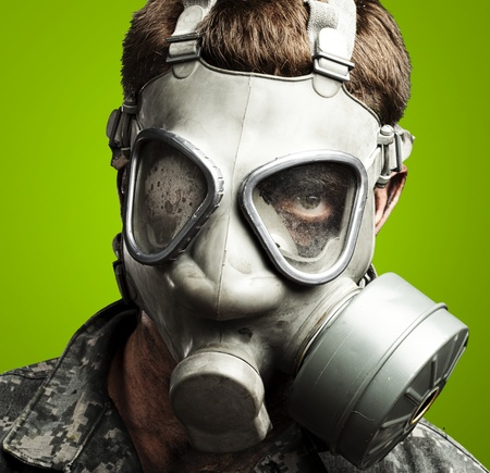 respirator: portrait of young soldier wearing gas mask against a green background
