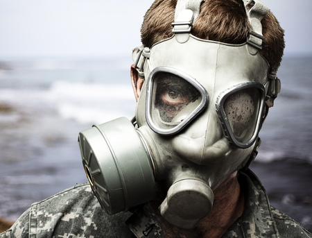 portrait of young soldier wearing gas mask against a sea background photo