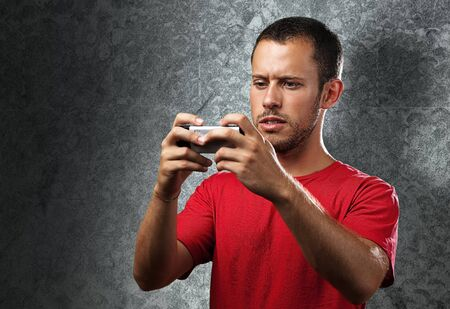 young man typing on mobile phone against a grunge wall photo