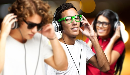 listening to music: retrato de los j�venes que tienen un partido contra un luces doradas Foto de archivo