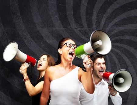 mensen schreeuwen met megafoon tegen een grunge muur