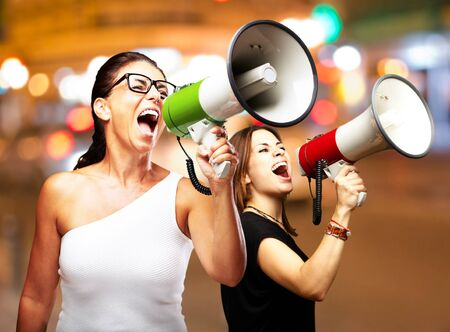 people shouting with megaphone at city by night Stock Photo - 12656282