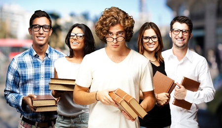 portrait of young students holding books at street photo