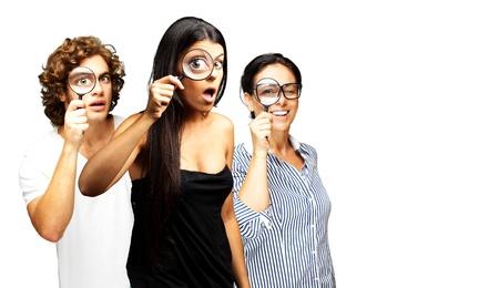jonge Scientifics kijken door een vergrootglas op een witte achtergrond