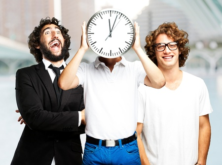 young man holding clock with friends at city photo