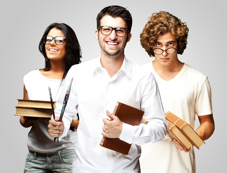 portrait of young students holding books over grey background photo