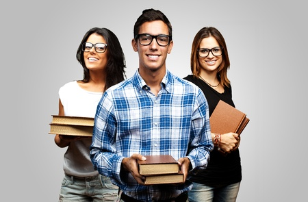 young students holding books over grey background photo