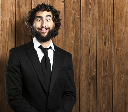 funny hair: portrait of young business man showing tongue against a wooden wall Stock Photo