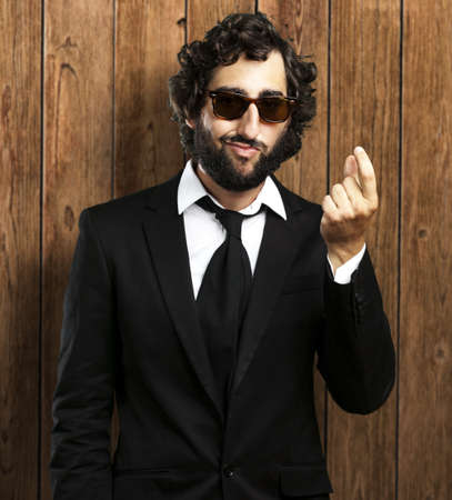 portrait of business man doing money sign against a wooden wall Stock Photo - 12656480