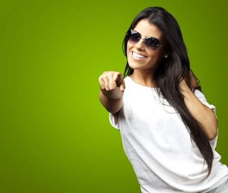 portrait of young woman wearing heart sungalasses pointing against a green background photo