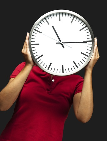 working late: woman holding clock in front of head against a black background Stock Photo
