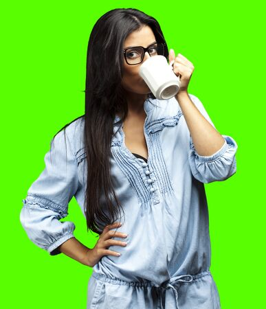 portrait of young woman drinking coffee against a removable chroma key background photo