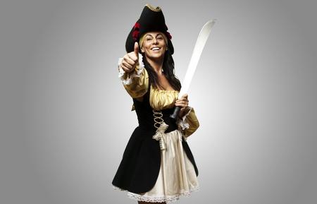 mujer pirata: retrato de una mujer pirata sosteniendo una espada y un gesto bien contra un fondo gris