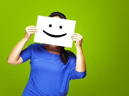 caras felices: Mujer mostrando un emoticon feliz delante de la cara sobre un fondo verde Foto de archivo