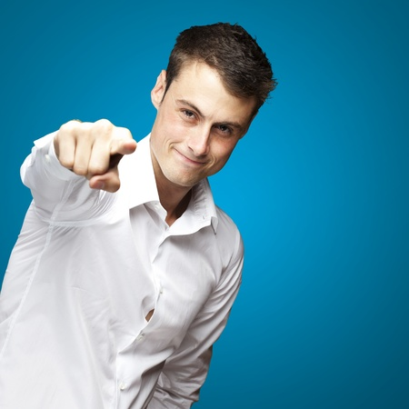 portraiit of young man pointing with finger against a blue background Stock Photo - 12656447