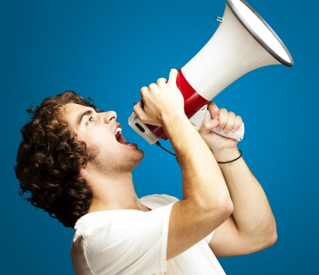 portrait of a handsome young man shouting with megaphone against a blue background photo
