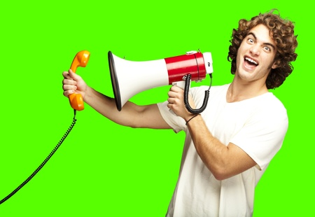 joking: portrait of young man shouting with megaphone and talking on vintage telephone over a removable chroma key background Stock Photo