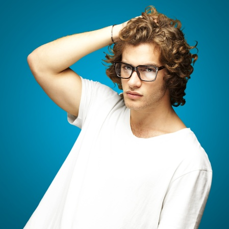 portrait of a handsome young man posing against a blue background Stock Photo - 12656415