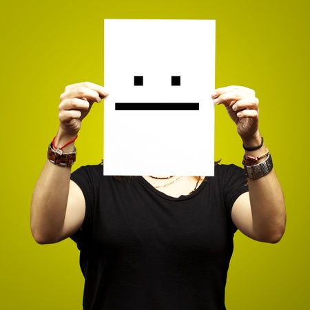 woman holding paper with poker face emoticon against a yellow background photo