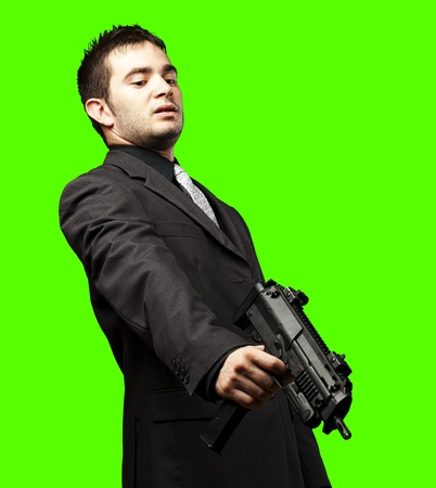 green screen: mafia man aiming down with gun against a removable chroma key background Stock Photo